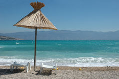 Vacation in Baska. Beach umbrella and pair of chairs on beach in Baska, island Krk, Croatia stock photography