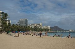 Vacation on the Beach. Families vacationing on the beach with Diamond Head Volcano overlooking the port of Honolulu at Oahu, Hawaii Royalty Free Stock Image