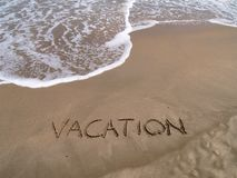 Vacation on the beach. Text vacation written on the sand Stock Image