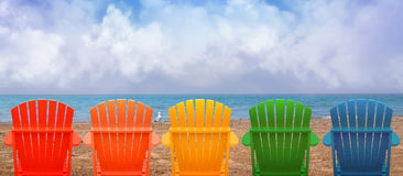 Vacation Beach Chairs on Sand. A rainbow of colors of wooden beach chairs are lined up along the water shore. There is copyspace in the clouds for a vacation Stock Photos