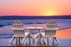 Vacation beach, chairs and table, San Diego. White chairs and table with cocktails on beach side walk, ocean sunset background. San Diego Coronado Island Beach stock images