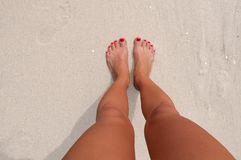 Vacation on the beach, feet on seashore. Female feet on sandy ocean beach. Vacation on the beach, legs on seashore Stock Photos