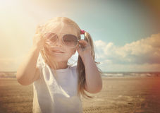 Vacation Beach Girl with Sunglasses in Warm Sun. A little retro girl in pigtails is wearing sunglasses at a sandy beach with warm sun shine on her face for a stock photo