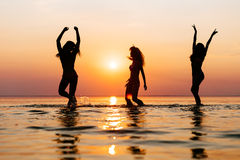 Vacation. Beach Party. Teenage girls having fun in water. Group of happy young people dancing at the on beautiful summer royalty free stock photography