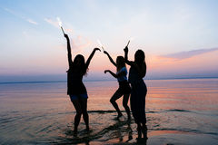Vacation. Beach Party. Teenage girls having fun in water. Group of happy young people dancing at the on beautiful summer Stock Images