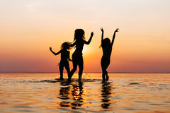 Vacation. Beach Party. Teenage girls having fun in water. Group of happy young people dancing at the on beautiful summer. Sunset. Silhouettes teen jumping royalty free stock images