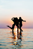 Vacation. Beach Party. Teenage girls having fun in water. Group of happy young people dancing at the on beautiful summer sunset. Stock Photo