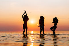 Vacation. Beach Party. Teenage girls having fun in water. Group of happy young people dancing at the on beautiful summer sunset. S Royalty Free Stock Image