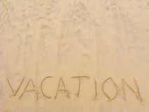 Beach Sand Writing Vacation. Word Vacation written on wet beach sand; Copy space Stock Images