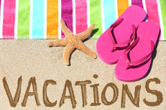 Vacation beach travel text. Concept. VACATIONS written in sand with water next to beach towel, summer sandals and starfish. Summer and sun vacation holidays Stock Photo
