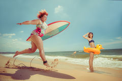 Vacation. Beautiful young fat women is runing to the summer sea with the surfboard Royalty Free Stock Photos