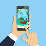 Vacation booking icon. Hands holding phone with beautiful tropical beach picture on screen Royalty Free Stock Images