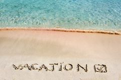 Vacation and checked mark written on sand on a beautiful beach, blue waves in background Royalty Free Stock Photos