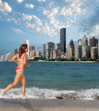 Vacation Choices. Woman at the beach, with a distant view of Midtown manhattan Stock Photo