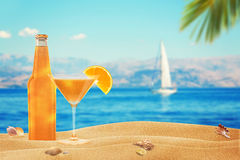 Vacation with a cocktail on the beach. Yacht and sea in the background Royalty Free Stock Image