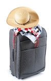 Vacation concept. Straw hat with swimwear on travel bag, isolated over white Royalty Free Stock Photos