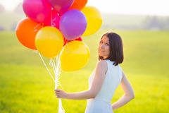Vacation concept. Girl half-turned to camera holding colorful ba. Vacation concept. Pretty girl half-turned to camera holding colorful balloons. Smiling young Stock Photo