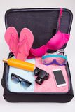 Vacation concept - open suitcase full of travel items Stock Photo