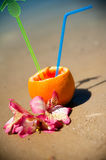 Vacation concept - orange with coctail straw and exotic flowers on the beach Royalty Free Stock Photo