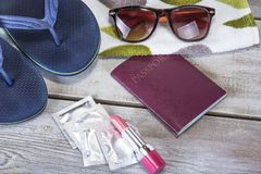 Vacation concept. Summer beach background with sunglasses, slippers, passport, condoms, copy space. Vacation concept. Summer beach background with sunglasses Stock Image