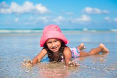 Vacation concept. Young girl with pink hat in blue water ocean royalty free stock photography
