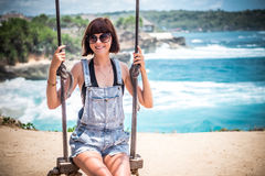 Vacation concept. Young woman swing on a beach swing on the cliff. Selective focus. Tropical island Nusa Lembongan Royalty Free Stock Photography
