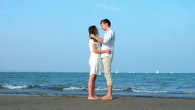 Vacation Couple at beach romantic holding hands and kissing.  stock footage