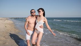 Vacation couple in love on exotic islands, lovers guy and girl walking barefoot on sand, beach panorama, happy friends. Hug and have fun during summer Rest stock video