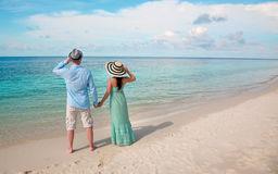 Vacation Couple walking on tropical beach Maldives. Royalty Free Stock Images