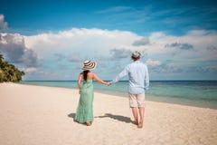Vacation Couple walking on tropical beach Maldives. Stock Photos