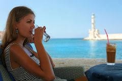 Vacation in Crete. A girl drinks cold water and frape. Cafe in port Chania, Crete, Greece Royalty Free Stock Photos