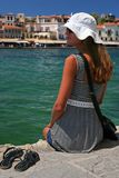 Vacation in Crete. A girl with white hat sits on bankment. Port in Chania, Crete, Greece Royalty Free Stock Photo