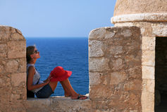 Vacation in Crete. A girl with red hat sits on a wall of a fortress. Rethymno, island Crete, Greece Royalty Free Stock Images