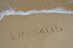 Vacation Dreams. Dreams written in sand on beach with waves in background - vacation royalty free stock photos