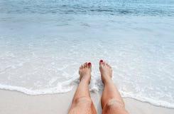 Vacation en la playa, pies en la costa Fotografía de archivo