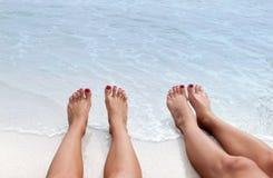 Vacation en la playa, pies en la costa Imagen de archivo libre de regalías