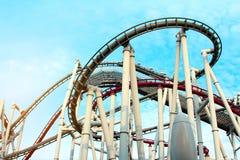 Vacation et appréciez les montagnes russes en acier de concep, rouges et blanches en parc d'attractions avec le ciel bleu lumineu photographie stock