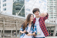 Vacation and friendship concept Selfie smiling asian girl and foreign boy friends with city guide map and backpack in Royalty Free Stock Images