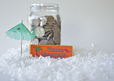 Vacation fund for winter holiday. A jar of coins/change, and a sign saying Think Vacation are nestled in some snow with a green umbrella. Image shows how Stock Images