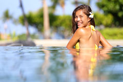 Vacation getaway woman swimming in a tropical pool. Smiling beautiful woman wearing a bikini relaxing in pool looking back over her shoulder across the Stock Photos