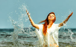Vacation. Girl splashing water having fun on the sea. Royalty Free Stock Photos