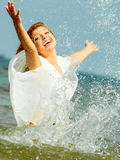 Vacation. Girl splashing water having fun on the sea. Royalty Free Stock Images