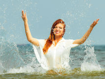 Vacation. Girl splashing water having fun on the sea. Stock Images