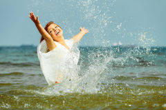 Vacation. Girl splashing water having fun on the sea. Royalty Free Stock Photography