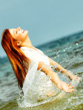 Vacation. Girl splashing water having fun on the sea. Stock Photography