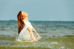 Vacation. Girl splashing water having fun on the sea. Stock Photo