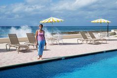 Vacation On Grand Cayman. The girl standing by the resort pool on Grand Cayman island, Cayman Islands stock photography