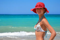 Vacation in Greece. Beautiful girl with rad hat enjoy sun by azure sea. Crete, Greece Stock Photo