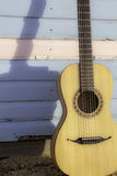 Vacation Guitar. Parlour-sized classical acoustic guitar resting against a beach hut painted in pastel pink and blue. Symbolic of vacation and beach relaxation Royalty Free Stock Image