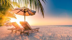 Vacation holidays background wallpaper, two beach lounge chairs under tent on beach. Beach chairs, umbrella and palms on the beach. Beautiful beach landscape Royalty Free Stock Photo